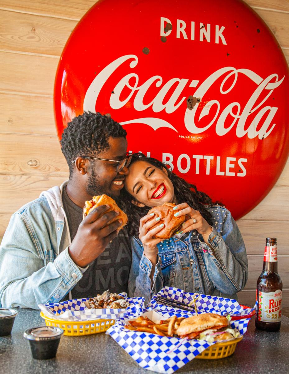 Couple eating burgers with a Coca-Cola sign behind them
