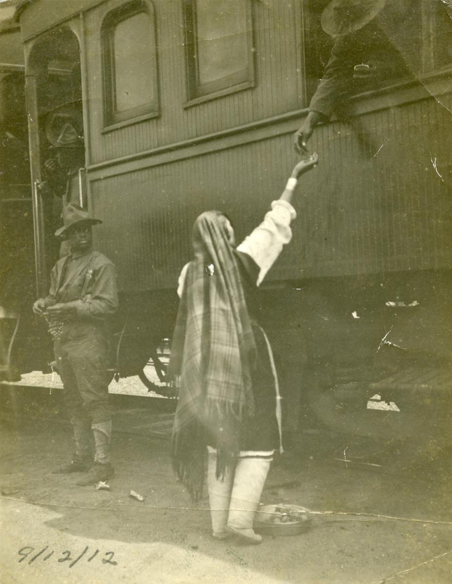 An Isleta Pueblo woman sells fruit to a soldier on a passenger train, 1912, New Mexico Magazine