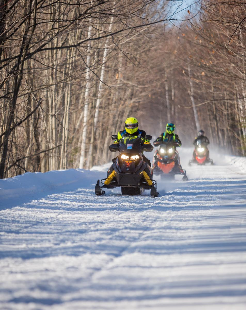 Three People Riding Snow Mobiles In Big Bay