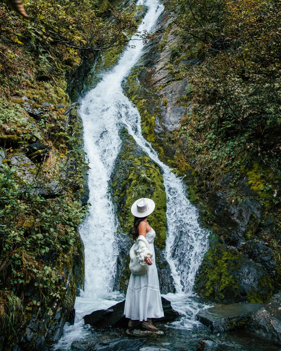 a woman in a brimmed hat and dress standing in front of a waterfall