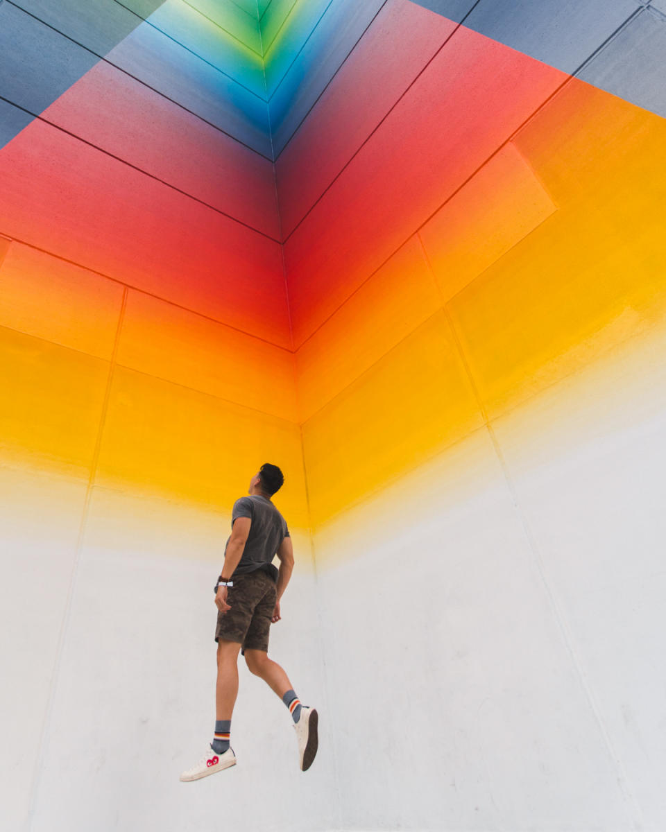 man jumps in front of Tau Ceti rainbow Mural in downtown Austin texas