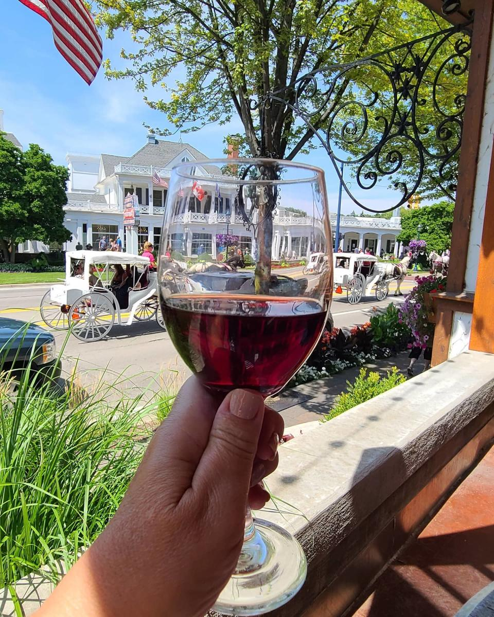 Enjoying a glass of wine on the patio of Bavarian Inn Restaurant while watching a horse-drawn carriage go by in front of Zehnder's of Frankenmuth