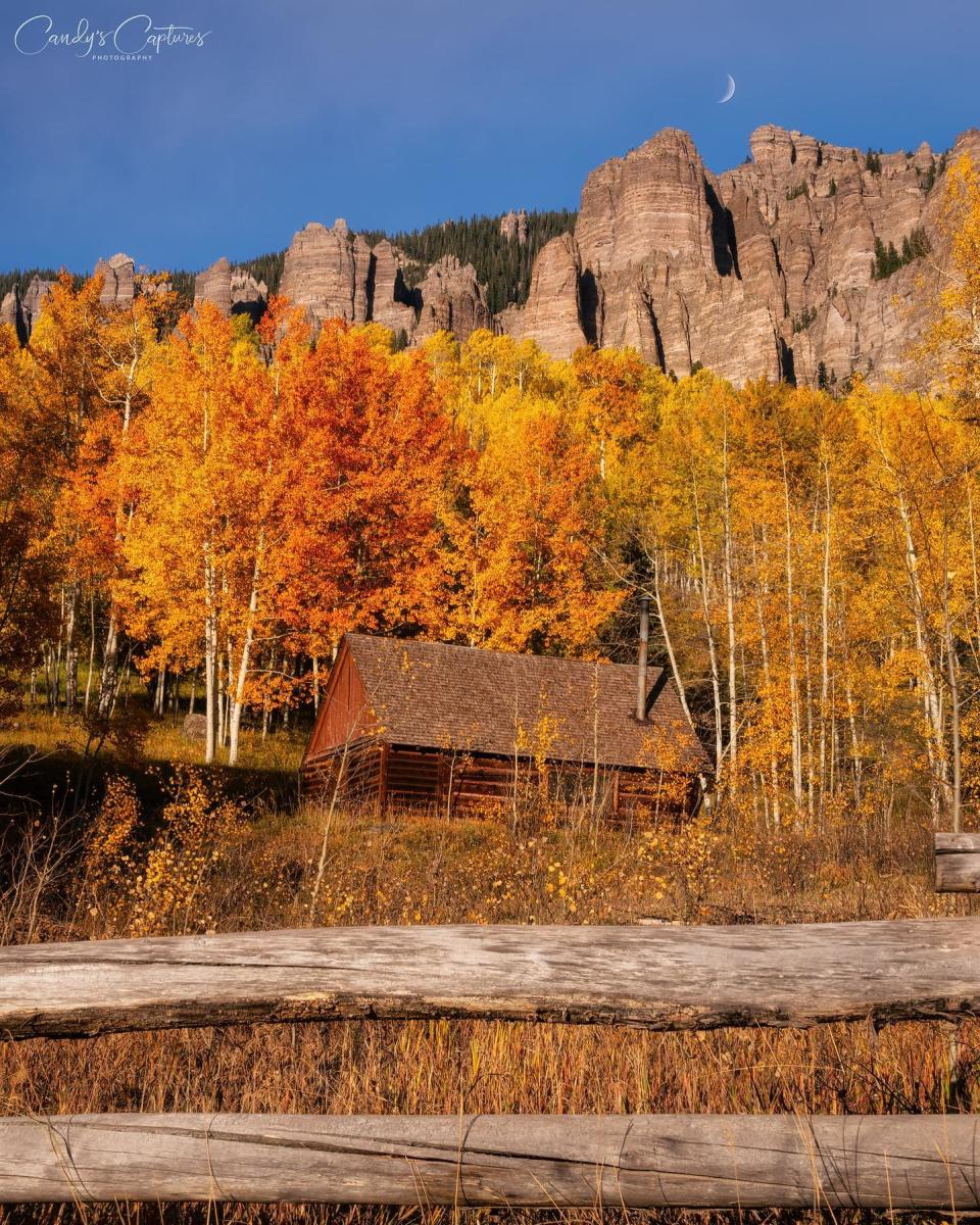 @CandysCaptures Cabin surrounded by yellow and orange aspens with mountains on Owl Creek Pass