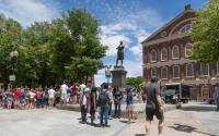 A group of visitors pause at the Samuel Adams statue outside Faneuil Hall