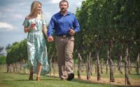 Couple Walking Through Grape Creek Vineyards In Fredericksburg, TX
