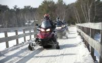 A group heads into the Minocqua wilderness on their snowmobiles.
