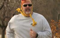 Guy running in Run with the Turkeys 5K/10K with Turkey hat