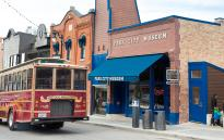 Trolly driving down historic main street, passing by a brick building with Park City Museum written on it.