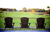 Three Adirondack chairs overlook the beautiful greens at LPGA International world-class golf course