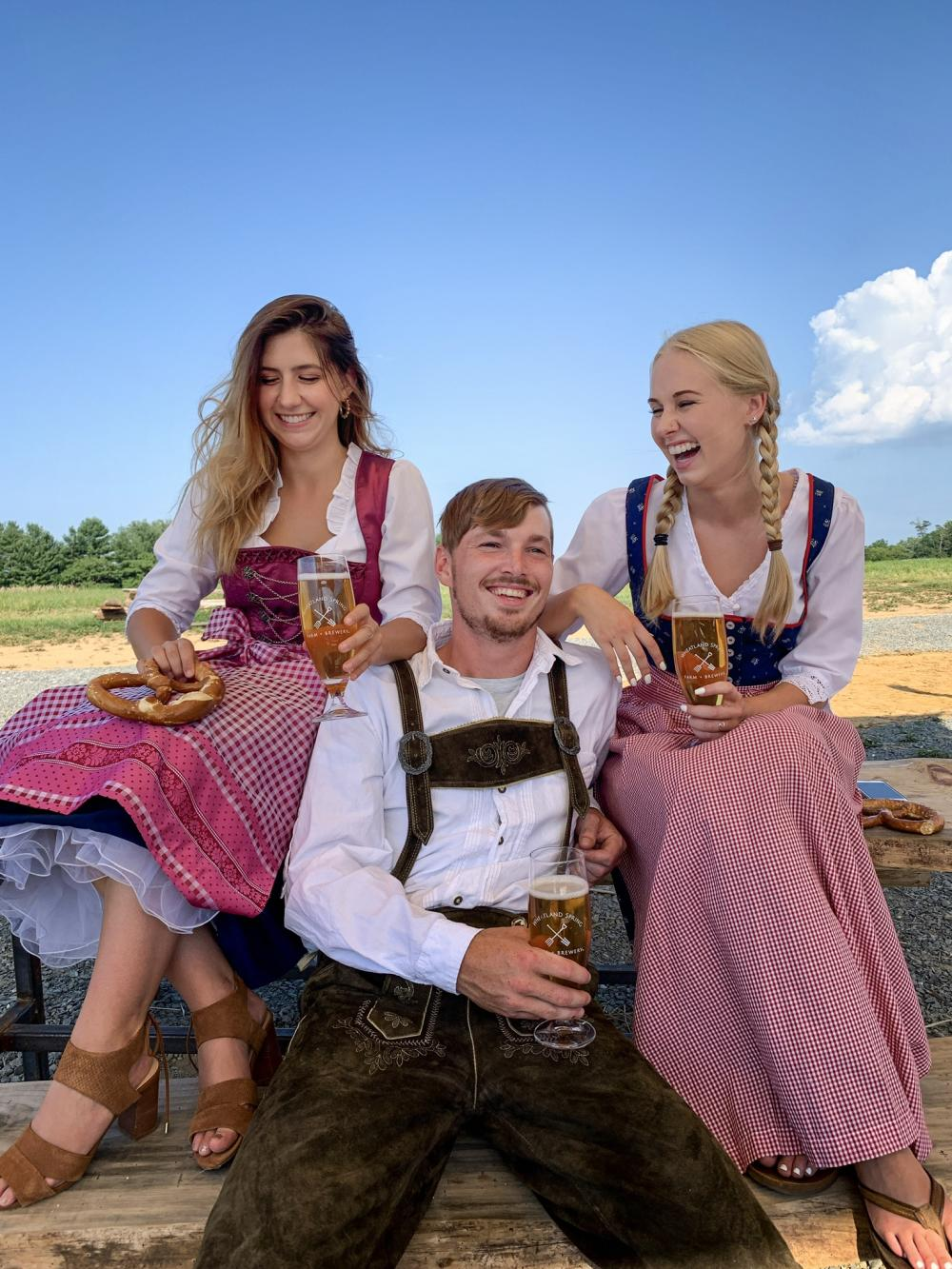 A man and two women laughing with beer in hand for Oktoberfest