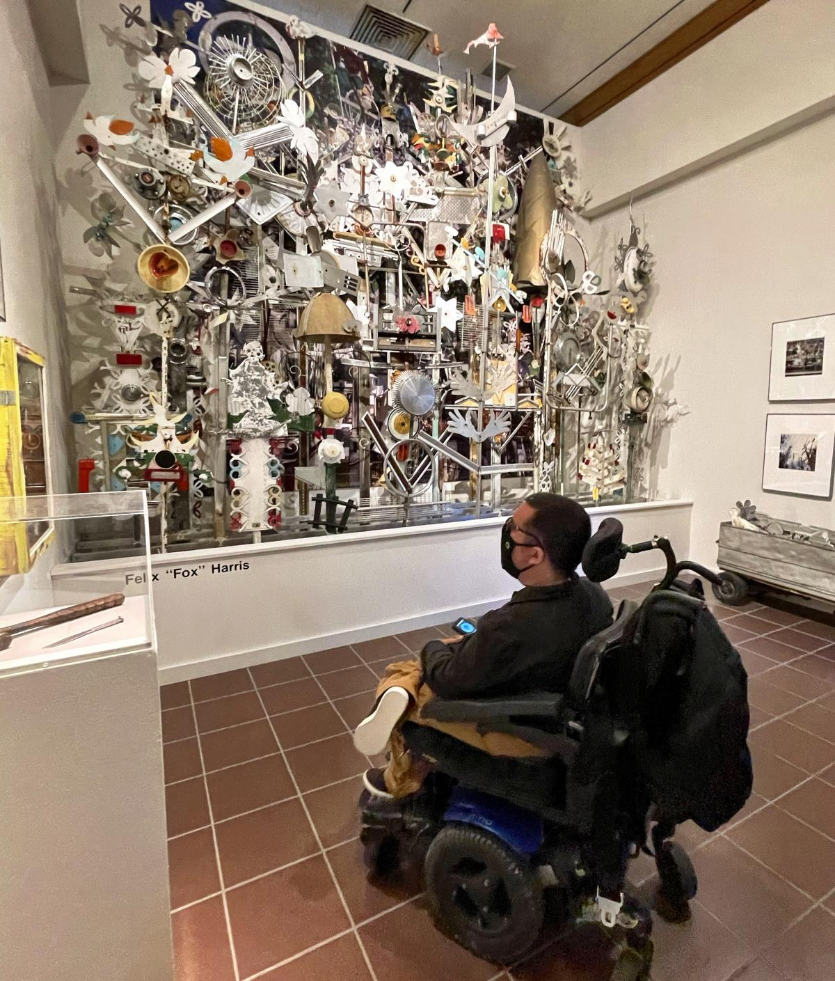 """Cory in front of piece by Felix """"Fox Harris: A stunning sculpture made of scrap metal and old toys."""