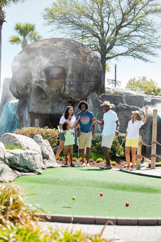 Multi-Gen Family Playing Mini Golf