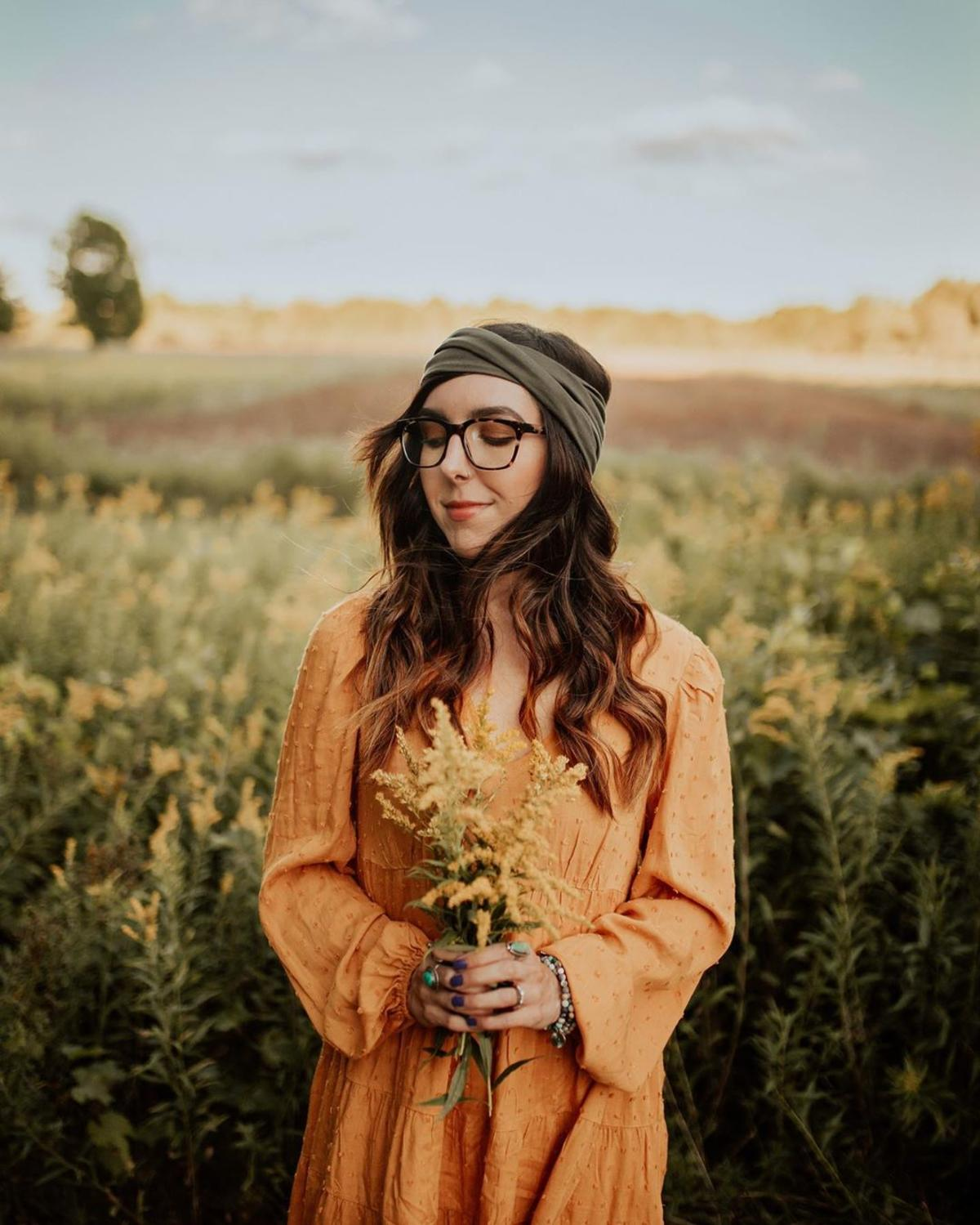 Woman holding a bundle of flowers in a field at Chippewa Nature Center in Midland