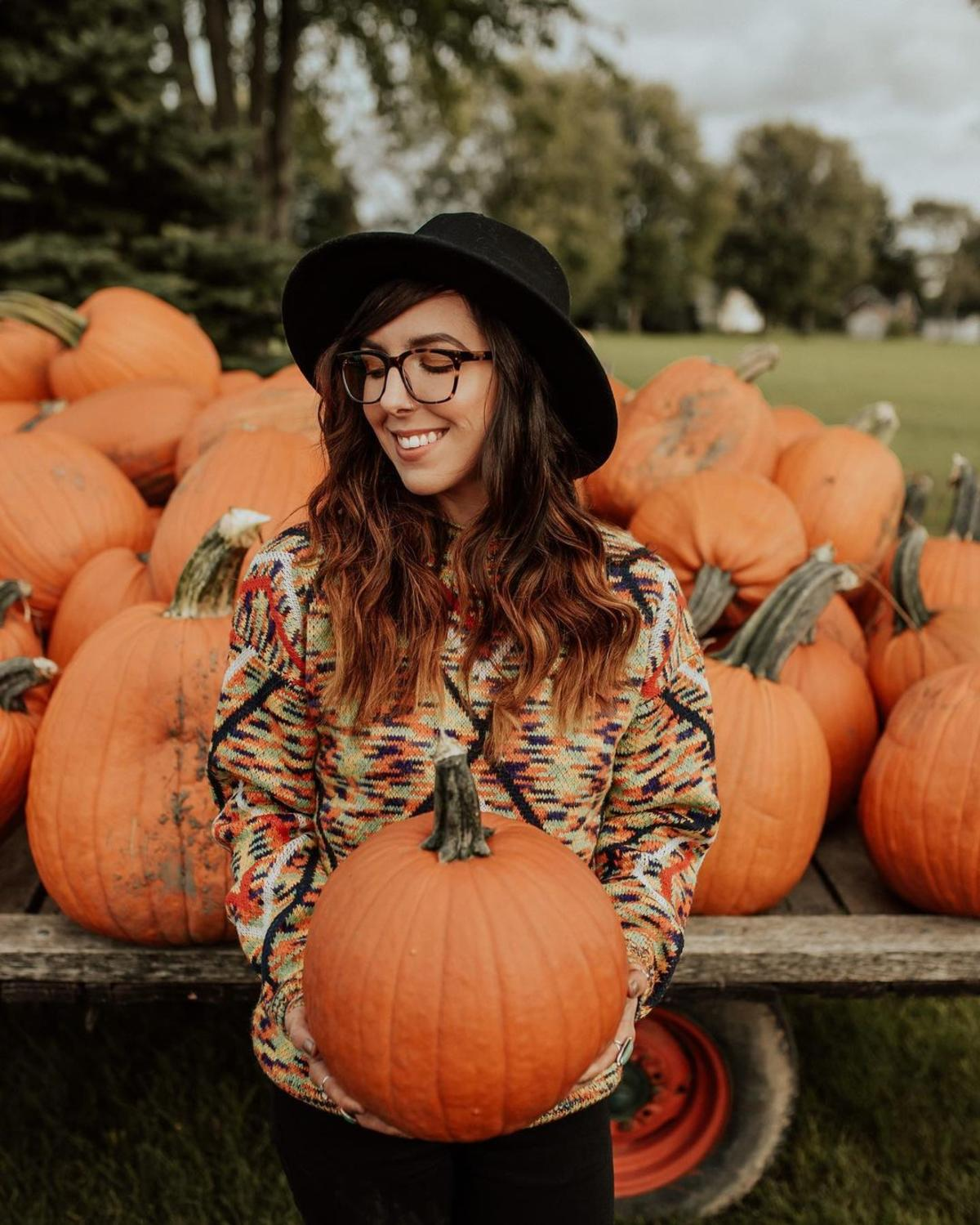 Woman smiling & holding a pumpkin in front of a trailer filled with them at Johnson's Giant Pumpkins in Saginaw