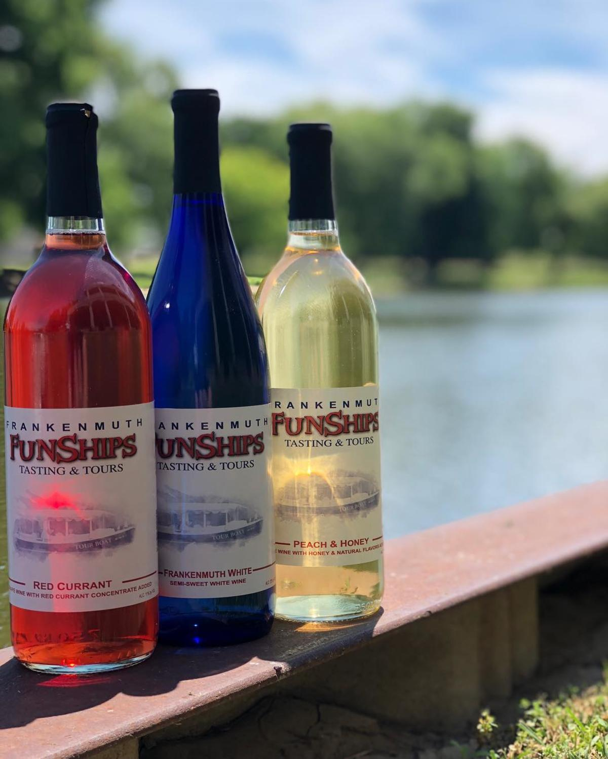 Three colorful bottles of Frankenmuth FunShips wine with a waterfront backdrop at Frankenmuth FunShips