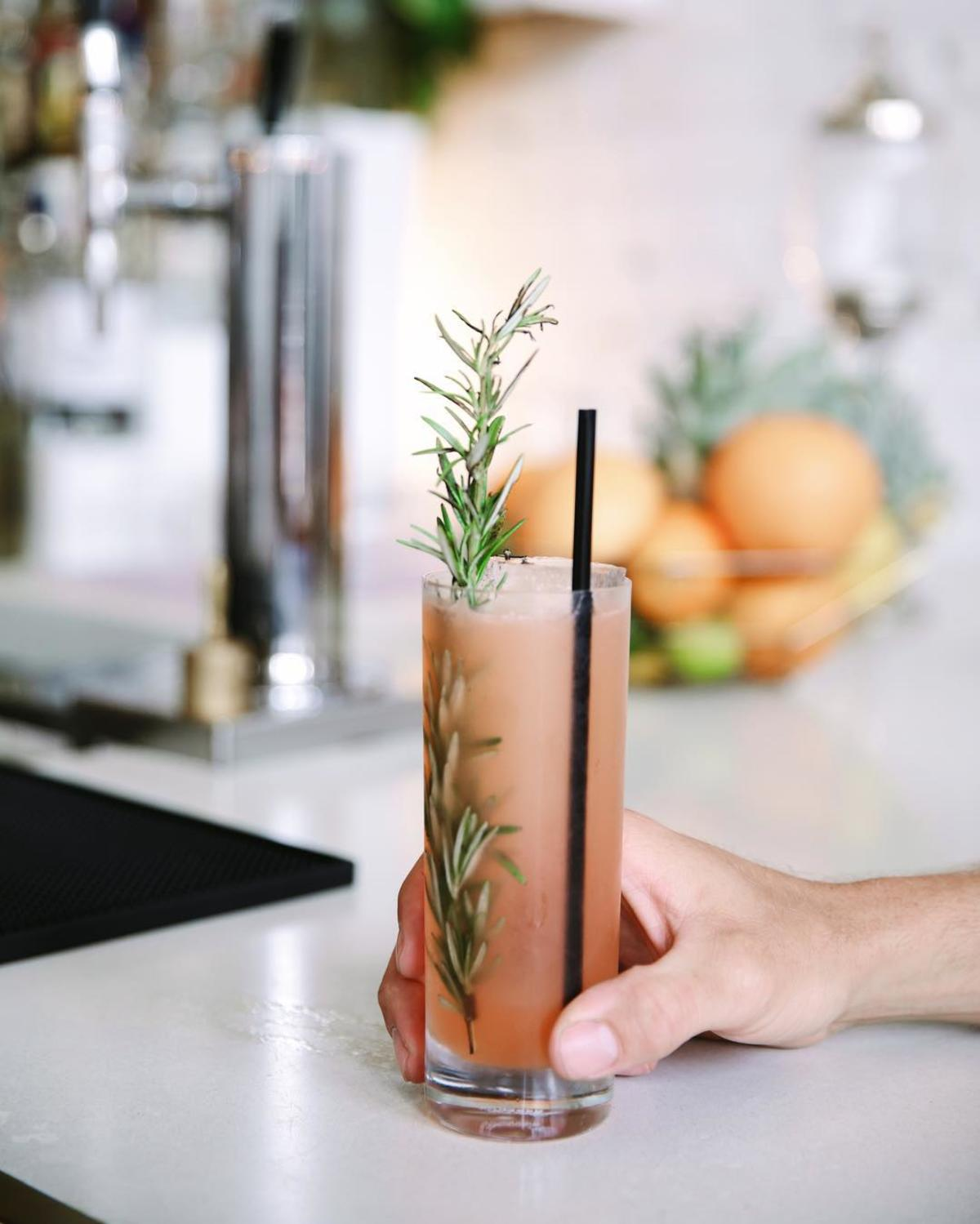 Peach-colored, summery drink with a sprig of fresh rosemary on the bar of The Public House in Bay City