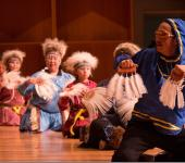 Alaska Native man and women dancing in traditional costumes