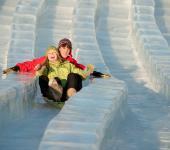 a boy and girl sledding on a mega ice slide