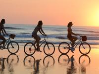 A group of female friends enjoy a sunrise bicycle ride on the beach