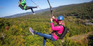 Two people ride a zipline over the forest at the Catamount ZipLine