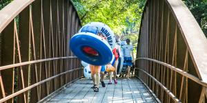 A group of people carrying inflatable tubes on the way to the Chattahoochee River.