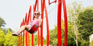 Charming little girl on the red swing set at Abernathy Greenway Playable Art Park