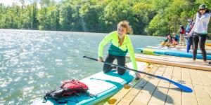 A female pushing off to do stand-up paddleboarding at High Country Paddle Shack in Sandy Springs, Ga at High Country Paddle Shack