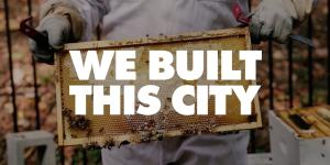 We Built This City logo (Mayor Rusty Paul holding a screened board from the hive with honey on it