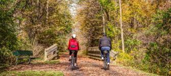 Couple bicycling on the Little Miami Scenic Trail in Fall