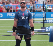 A CrossFit competitor lifts a dumbbell full of weight plates