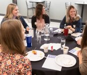 A table of attendees share a laugh while learning to navigate online reviews