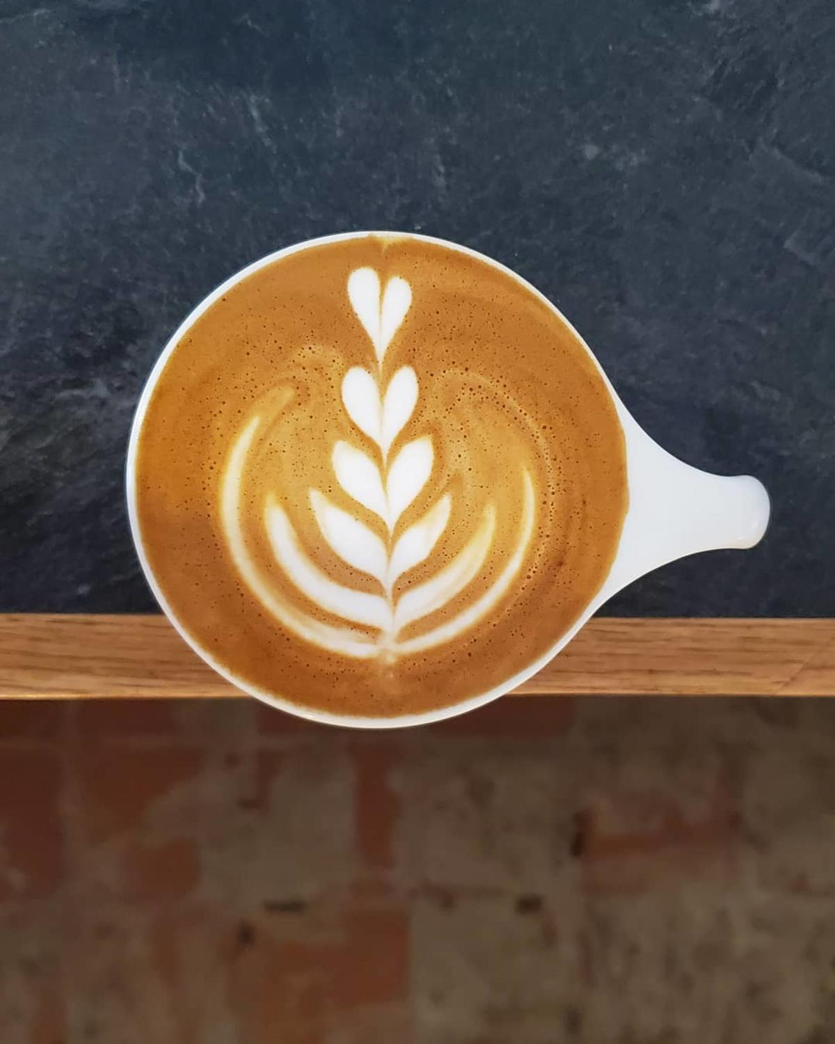 Beautiful cappuccino art in a mug on the counter at The Loch Coffee Company in Midland