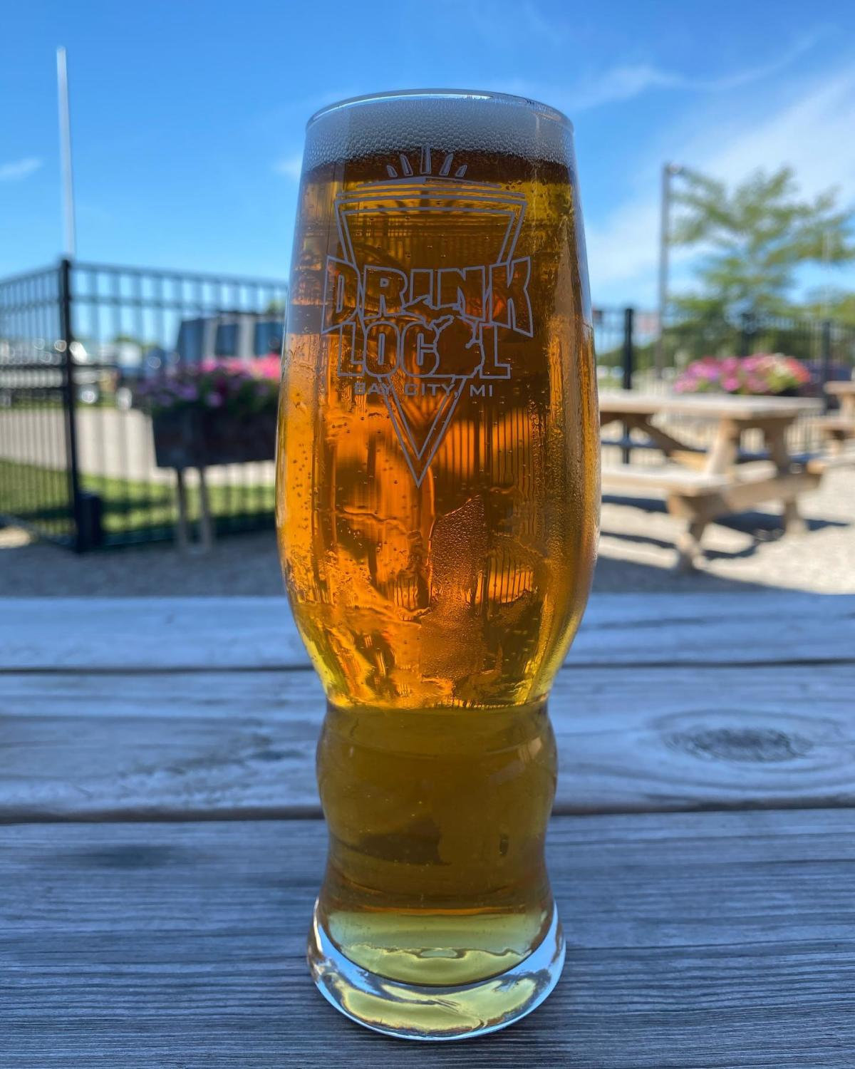 "Fresh pour served in a ""Drink Local"" pint glass on a summery day outside of Tri-City Brewing Company in Bay City"