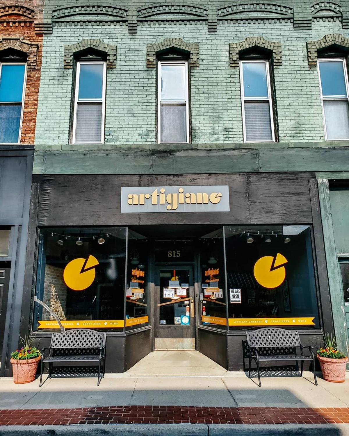 Colorful storefront view of Artigiano Artisan Cheese Shoppe building in Bay City