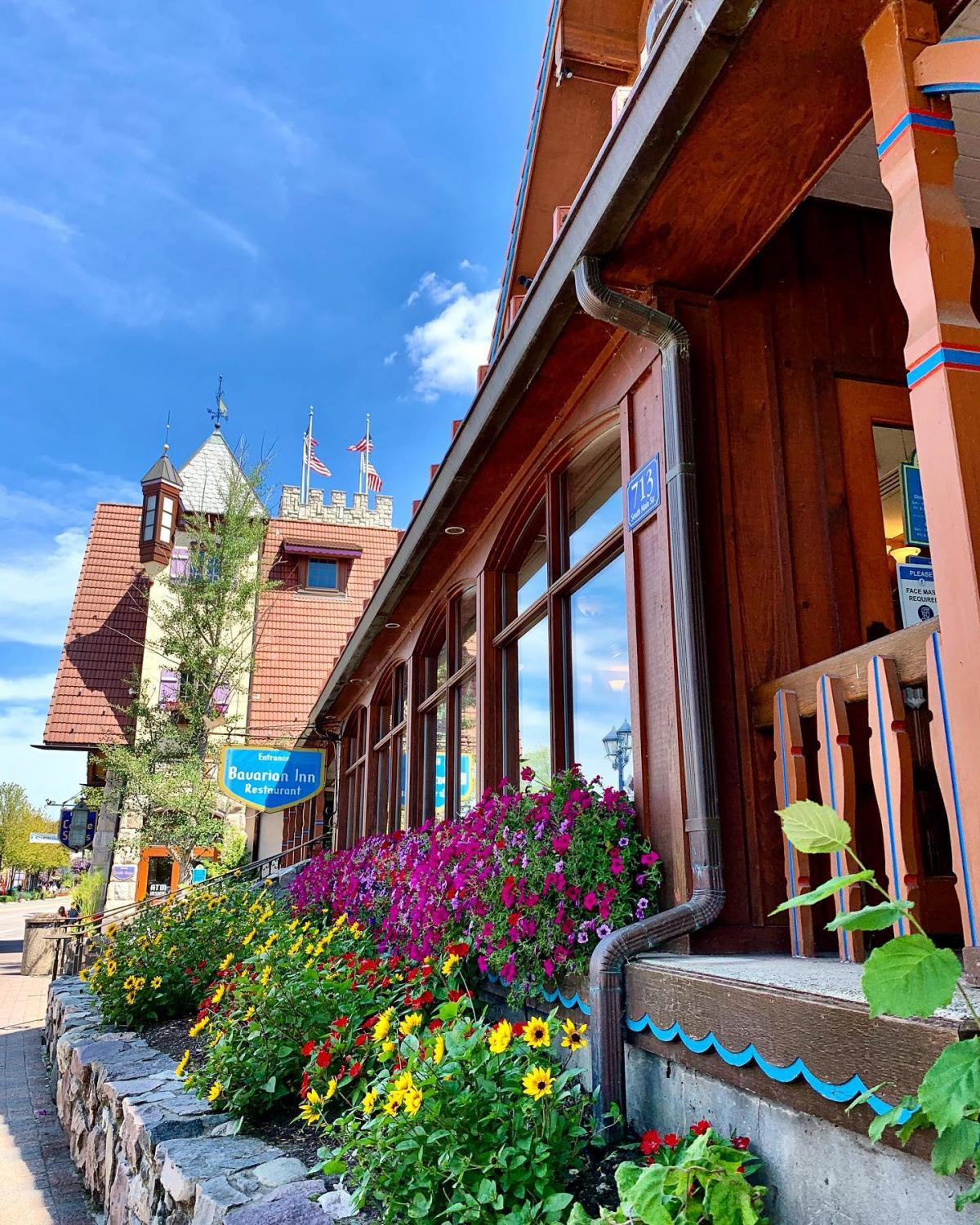 Summery street views of Bavarian Inn Restaurant in Frankenmuth, with beautiful flowers in bloom