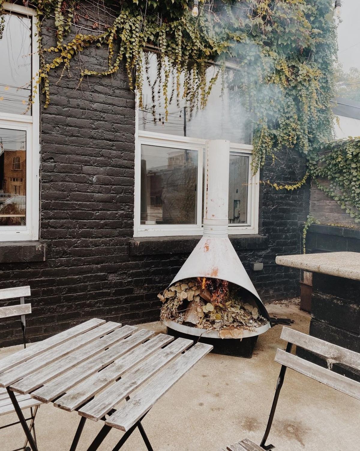 Wood-burning fire in a chimenea on the patio of Harless + Hugh Coffee in Bay City