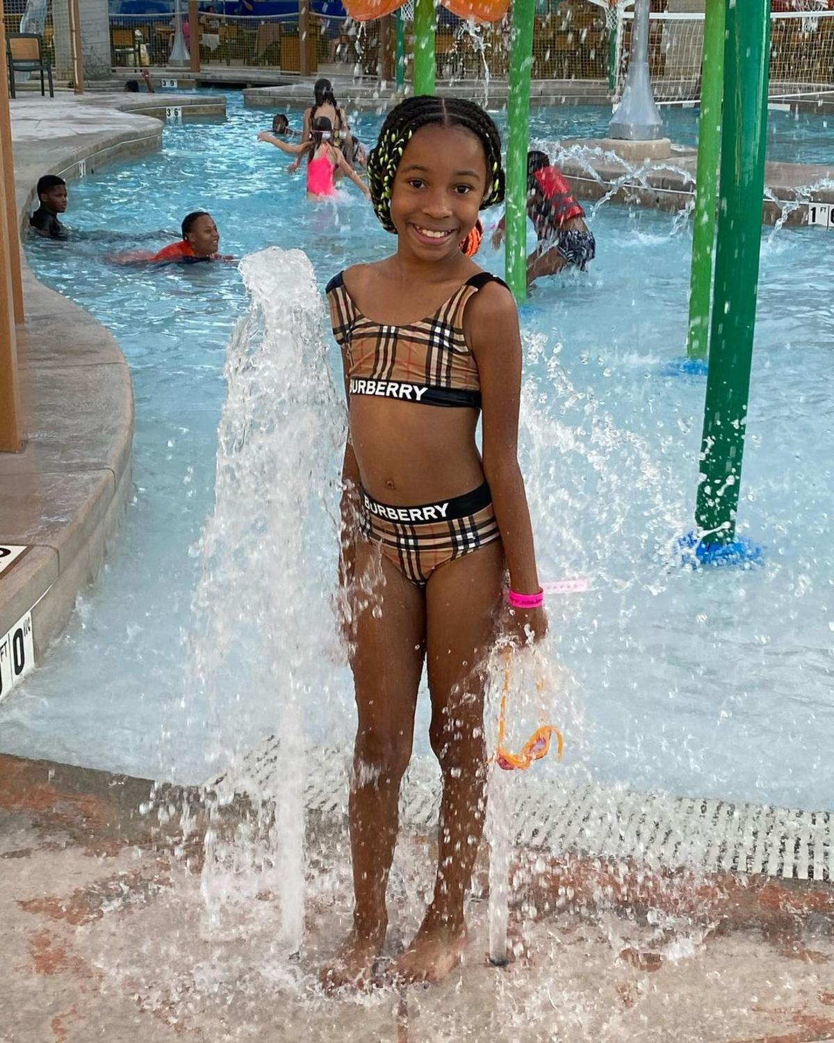 Little girl smiling by a splashing geyser in front of an indoor pool at Zehnder's Splash Village Hotel & Waterpark in Frankenmuth