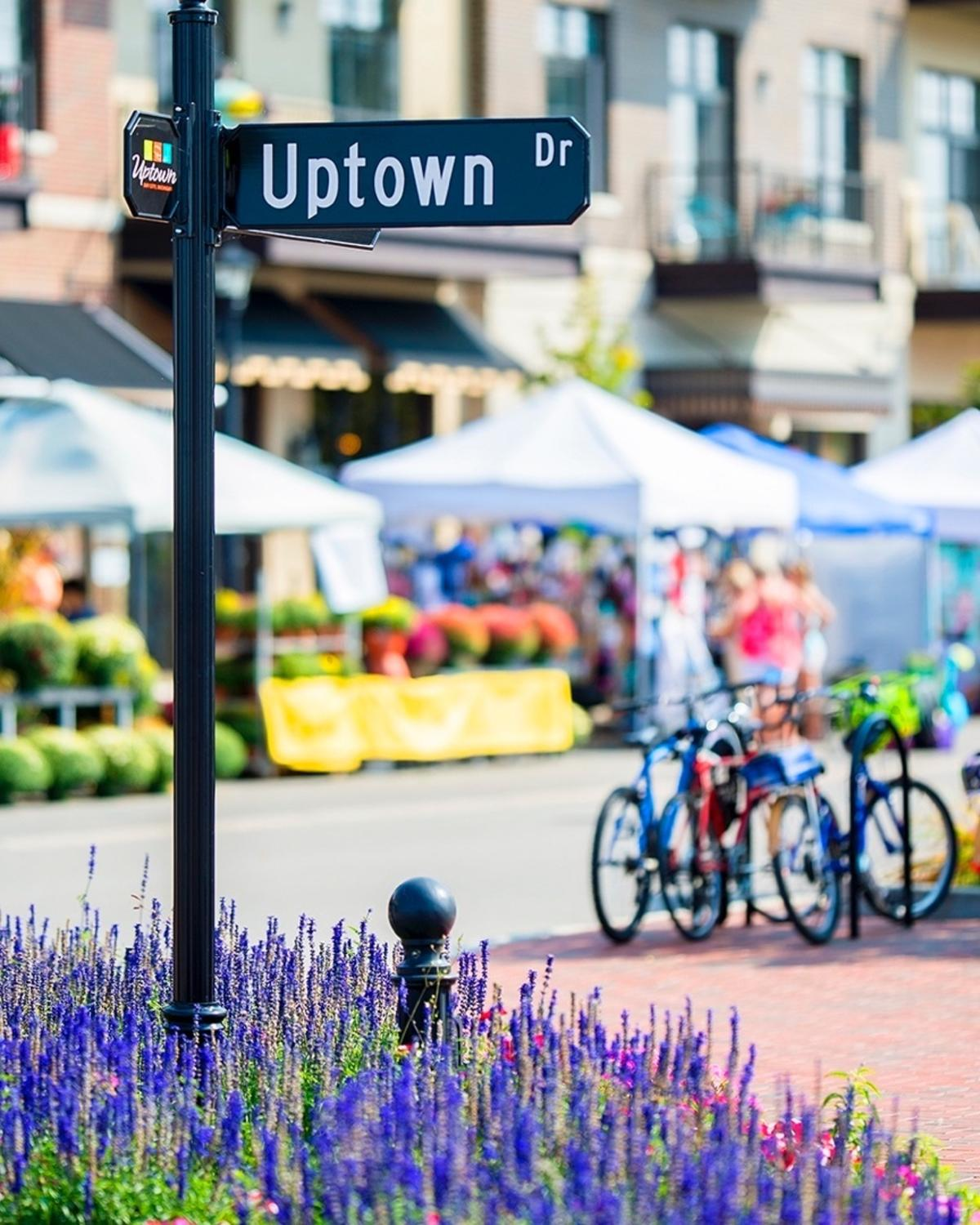 Tents set up by beautiful street plantings on Uptown Drive for The Great Lakes Market in Uptown Bay City