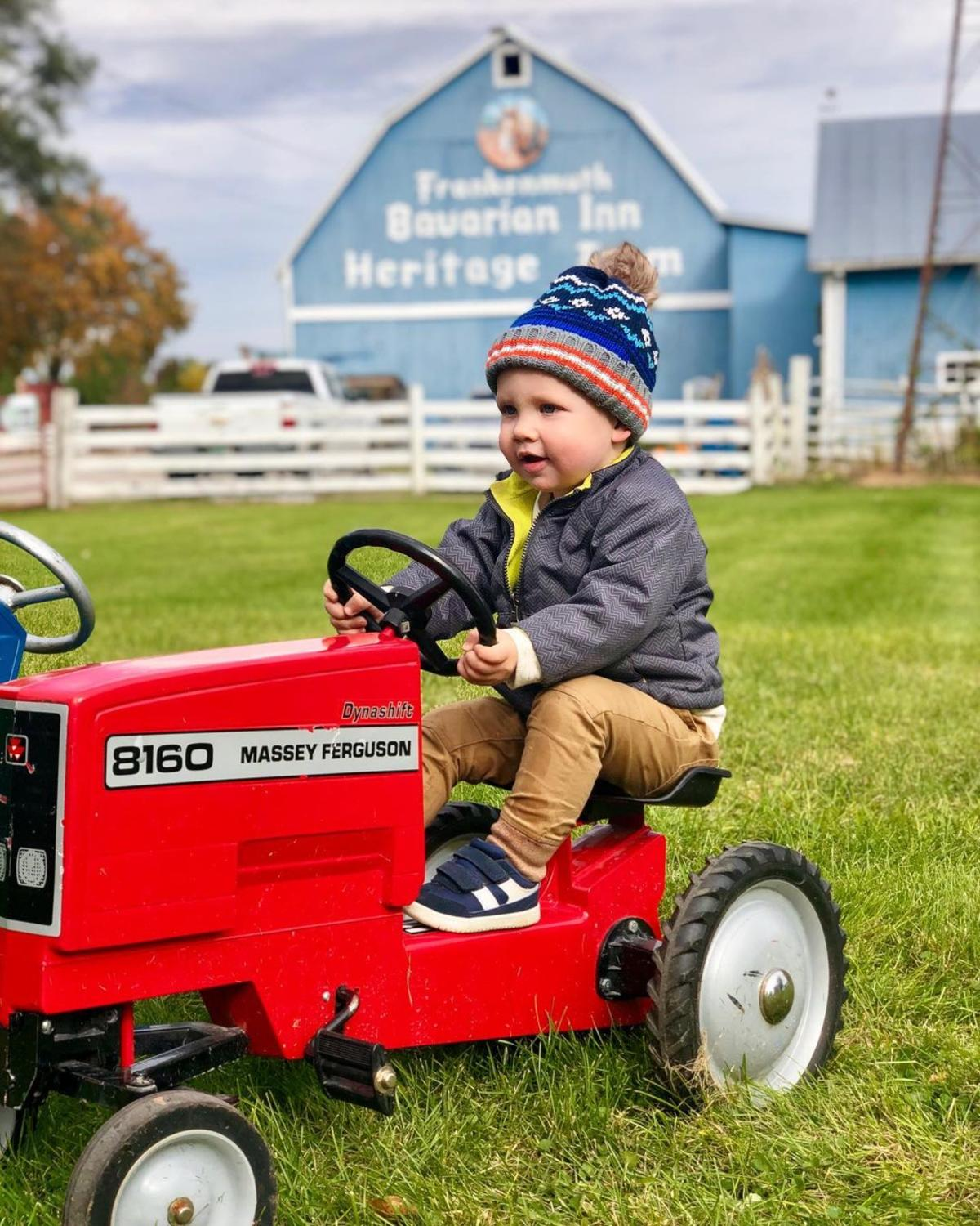 Little boy on a miniature red tractor at Grandpa Tiny's Farm in Frankenmuth, with a big, blue barn in the background