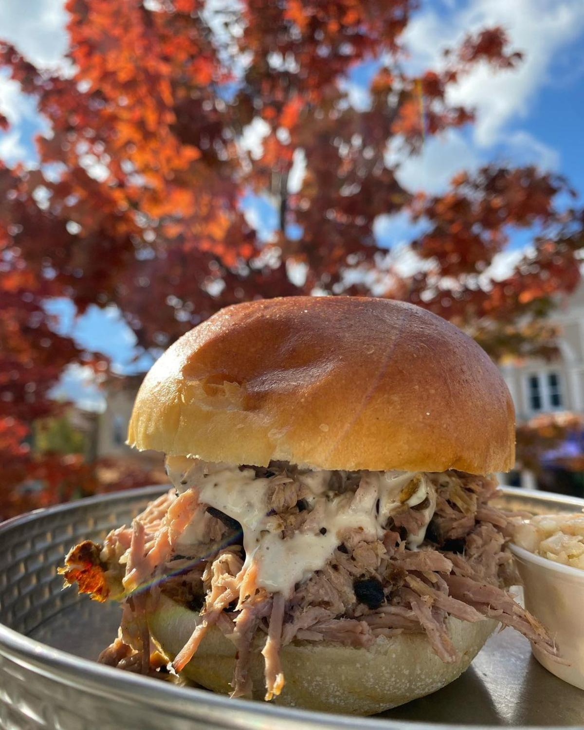 Heaping Carolina BBQ Pulled Pork Sandwich served up outside with a beautiful backdrop of fall trees at Molasses Smokehouse + Bar in Midland