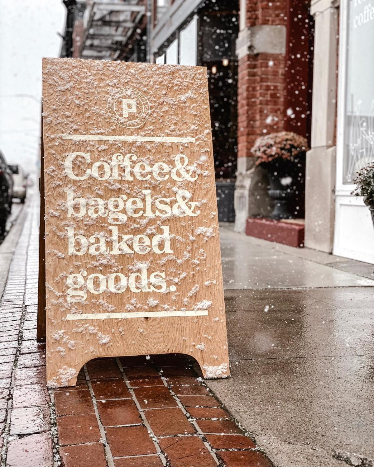 """Views of a sandwich board on the sidewalk that says """"Coffee & bagels & baked goods"""" with snow falling gently all around it at Populace Coffee in Bay City"""