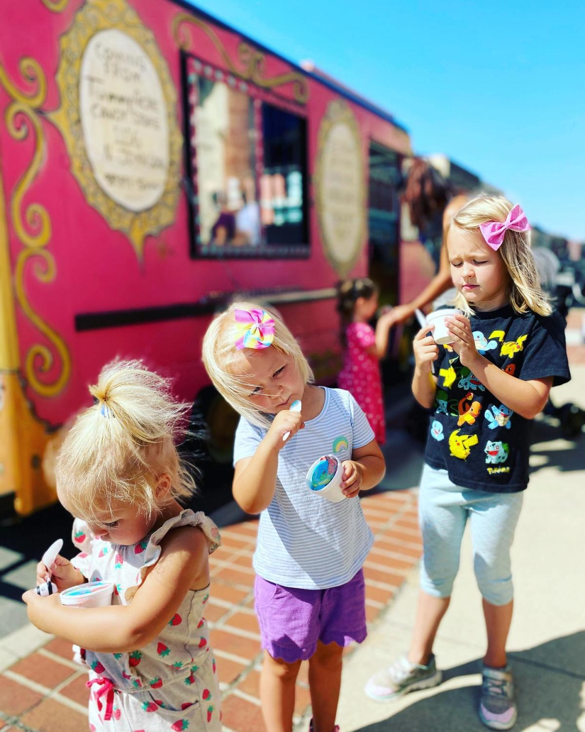 Little girls eating ice cream in front of a colorful ice cream truck by Tummy Ache Candy Store in Bay City