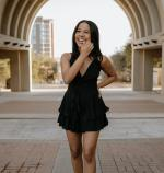 Photo of women in a black dress standing in an archway and smiling towards camera