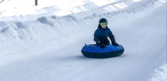 a boy rides a tube down a tubing lane