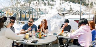Group of friends eating at bridge on the patio on a spring day apres ski