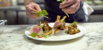 close up of hands plating a dish