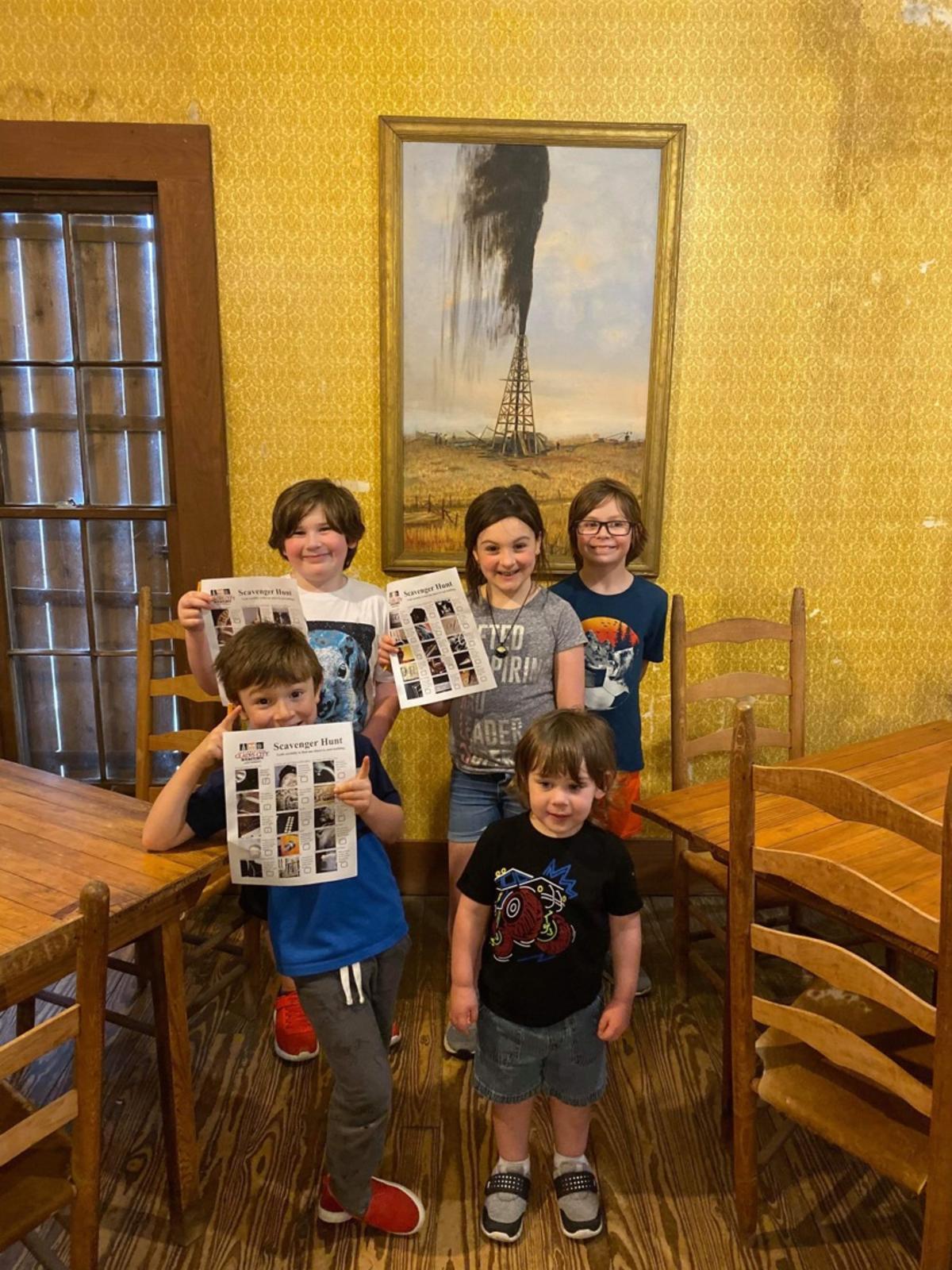 Kids holding up the Spindletop Scavenger Hunt sheet
