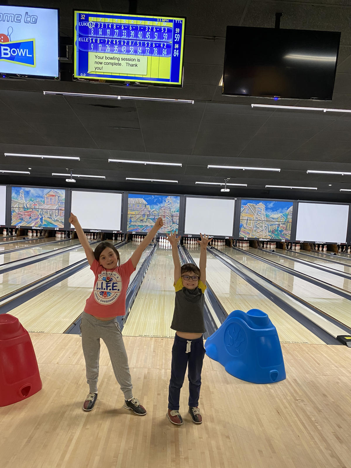 Two kids with their hands up in the air at Max Bowl
