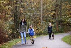 Mother and son walking on a trail with falling leaves