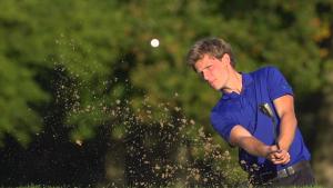 Man hitting a golf ball out of a sand trap in a Daytona Beach golf course